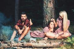 妇女的有胡子的人烘烤香肠葡萄酒礼服的 行家和女孩放松在森林男朋友厨师的篝火 免版税库存照片
