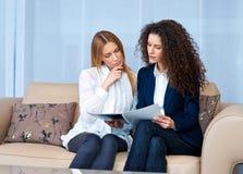 读妇女的朋友在家 免版税库存图片