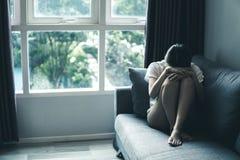 妇女的消沉和忧虑概念胎方位的在有阴沉的颜色的沙发 免版税图库摄影