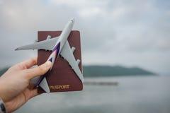 妇女的特写镜头手拿着飞机,并且护照有湖,天空, mou 免版税图库摄影