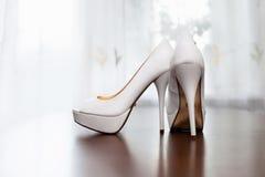 妇女的白色婚礼鞋子在地板上 免版税库存照片