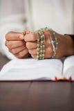 妇女的祈祷的手有一个念珠的在圣经 库存图片