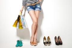 妇女的腿、购物袋和鞋子 免版税库存照片