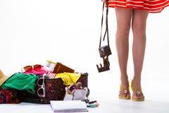 妇女的腿和被过度充填的手提箱 免版税库存照片