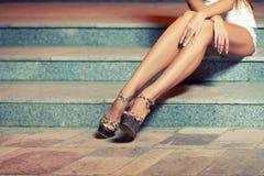 妇女的腿坐台阶 免版税库存照片