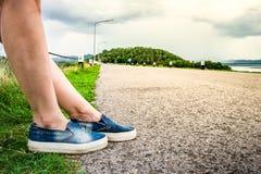 妇女的腿坐高速公路栏杆在路旁 免版税库存照片