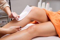 给妇女的腿打蜡的美容师 库存图片