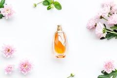 妇女的花卉香水 瓶在精美桃红色花附近的香水在白色背景顶视图样式 图库摄影