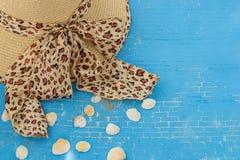 妇女的草帽有豹子印刷品的,在蓝色背景的贝壳 免版税库存照片