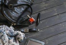 妇女的辅助部件-黑皮革提包、围巾、手表、指甲油、染睫毛油和片剂计算机 免版税库存照片