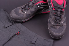 妇女的远足的靴子和长裤在黑背景 免版税库存图片