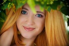 妇女的面孔到叶子里 图库摄影