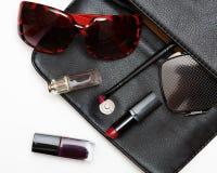 妇女的顶视图辅助部件 时髦的太阳镜,黑皮包,唇膏,香水,塑造在白色的平的位置 库存照片