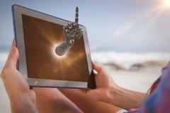 妇女的综合图象坐在轻便折叠躺椅的海滩使用片剂个人计算机 图库摄影