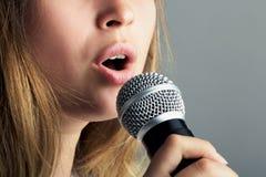 妇女的嘴的特写镜头唱歌入话筒的 图库摄影