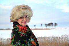 妇女的画象在毛皮盖帽和一件五颜六色的披肩半转动了反对冬天湖 库存照片