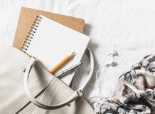 妇女皮革提包、干净的空白的笔记薄、笔和围巾在轻的背景,顶视图 空位 免版税库存照片