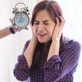 妇女盖她的耳朵从由闹钟声音注重  库存图片