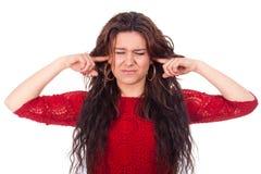 妇女盖她的耳朵和非常懊恼由噪声 免版税库存图片