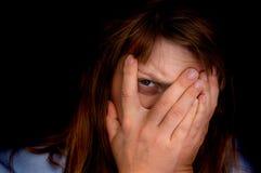 妇女盖她的面孔并且看与一只眼睛的照相机 免版税库存照片
