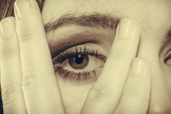 妇女盖子面孔神色通过手指 免版税库存照片