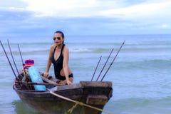 妇女相当黑比基尼泳装和小船在海滩 库存照片