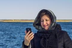 妇女看一个手机的屏幕 免版税库存图片