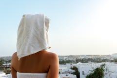 妇女看与一块毛巾的落日在她的头在俯视山的大阳台的一场阵雨以后 免版税库存照片
