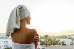 妇女看与一块毛巾的落日在她的头在俯视山的大阳台的一场阵雨以后 免版税库存图片