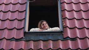 妇女看从一个开窗口的街道用他的在窗台的手 股票视频
