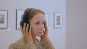 妇女看博览会的和在现代相集的听的音频指南 股票录像