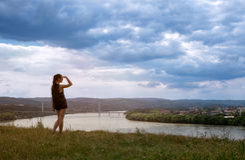 妇女看在城市的河 库存图片