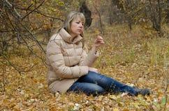妇女看在秋天黄色叶子的消沉 免版税库存图片