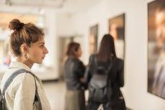 妇女看在美术画廊的小组现代绘画 免版税库存图片