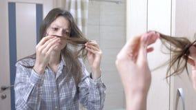 妇女看她的干燥,易碎的头发在卫生间里 股票视频