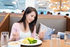 妇女看手机和吃午餐在restauara 库存照片