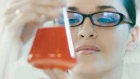 妇女看看烧瓶在实验室 股票录像