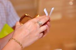 妇女看纸和香水气味在她的手上 免版税库存图片