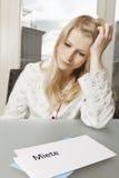 妇女看起来绝望在上写字 免版税图库摄影