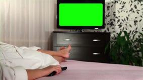 妇女看绿色被筛选的电视 影视素材