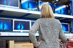 妇女看LCD电视在商店 库存照片