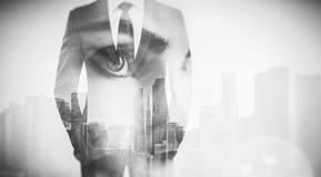妇女眼睛和商人照片在衣服 背景的两次曝光摩天大楼 黑色白色 库存图片