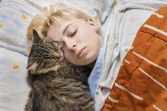 妇女睡着在与猫的床上 免版税图库摄影