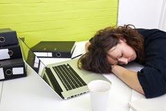 妇女睡着在她的书桌 库存图片