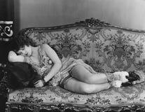 妇女睡着在长沙发 库存图片