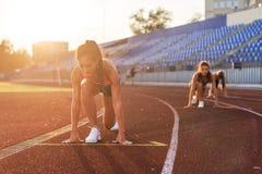 妇女短跑选手在开始状态准备好种族在跑马场 免版税图库摄影