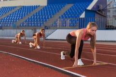 妇女短跑选手在开始状态准备好种族在跑马场 免版税库存图片