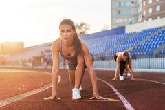 妇女短跑选手在开始状态准备好种族在跑马场 免版税库存照片