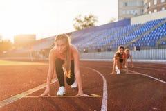 妇女短跑选手在开始状态准备好种族在跑马场 库存图片
