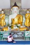 妇女祈祷前面菩萨雕象 免版税库存图片